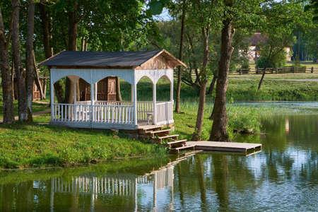 Summer gazebo on shore of pond. Wooden pergola in Merechevshchina, Tadeusz Kosciuszko birthplace, near Kossovo village Brest region, Belarus.