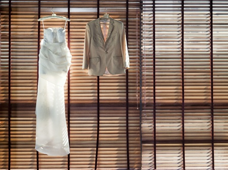 Wedding dress hanging on the wooden curtain