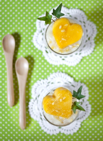 sticky rice in coconut cream with ripe mango heart shapes in glass on polka dots background  photo