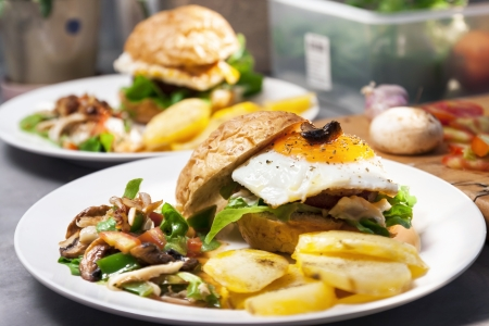 Egg burger , salad , boiled potatoes on kitchen background