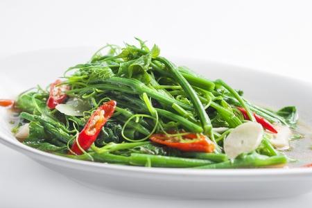 Stir-fried chayote in dish on wihte background  photo