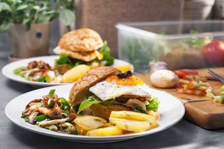 Egg burger , salad , boiled potatoes on kitchen    photo