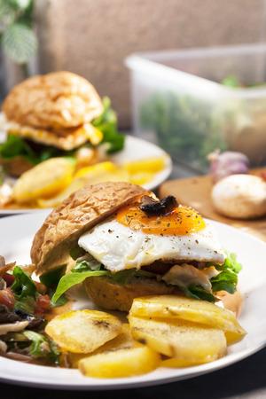 Egg burger, salade, pommes de terre bouillies sur fond de cuisine