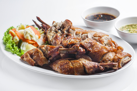 Fried duck with  hack in dish on white background  photo
