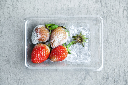 Strawberry with fungi in  plastic box on cement