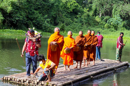 Oh Poi Market , Ratchaburi , Thailand - August 2020 : Buddhist  monks with monk's alms-bowl in hands standing on bamboo raft  with man blowing animal horn