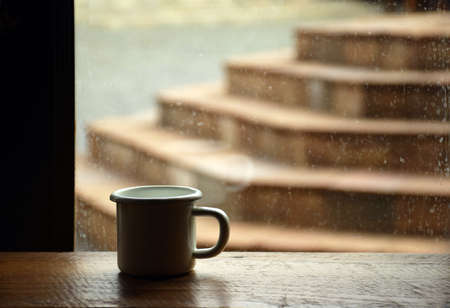 Coffee cup on wooden table near the window in cafe background Stock Photo