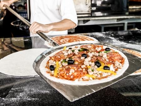 Close-up de hand van chef-kok bakker in witte uniform maken pizza