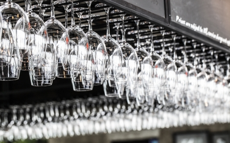 bar ware: Glasses hanging over a bar rack Stock Photo