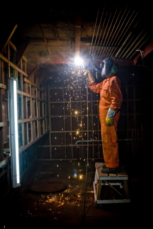 Metal wroker in a factory grinding with sparks Banque d'images