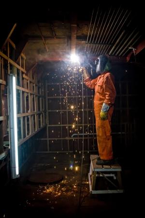 Metalen wroker in een fabriek slijpen met vonken Stockfoto