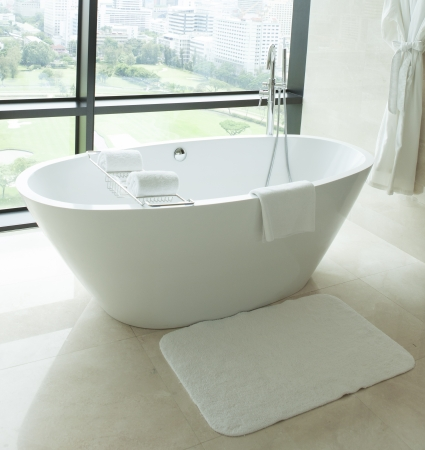 Claw foot bath in a white tiled bathroom Stock Photo