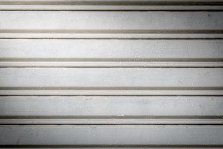 metal wall: illuminated grunge-metallic roller auto shutter door with light from corner