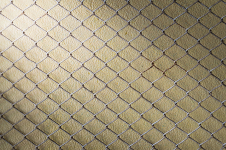 enclose: steel wire mesh fence wall background with light from corner Stock Photo
