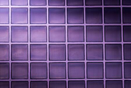 morado: Fondo de la pared de bloques de vidrio de color p�rpura con la iluminaci�n de la esquina
