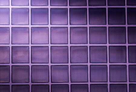 purple glass block wall background with lighting from corner