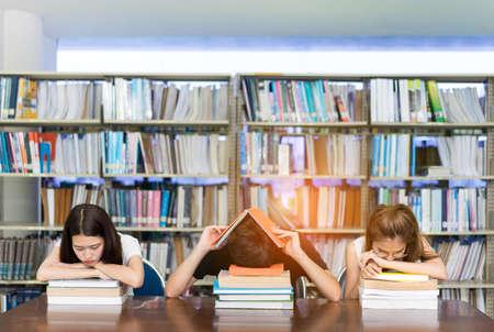 Jonge studentengroep serieus met haar examen en leesboek in de bibliotheek Stockfoto