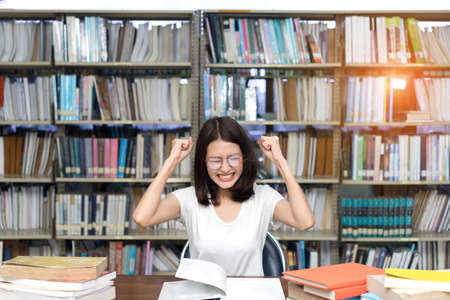 eyestrain: Young Girl Student  with Glasses Serious, Hard  Exam Reading Book in Classroom Education Library