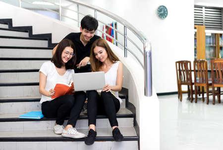 Jonge studentengroep leesboek en met behulp van Laptop Computer Glimlach in Classroom Onderwijs Bibliotheek Universitair Kenniscentrum Stockfoto