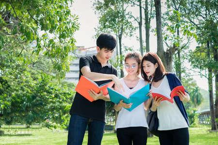 Groep jonge studenten op zoek naar schoolmappen in het onderwijs Campus University Outdoor Stockfoto