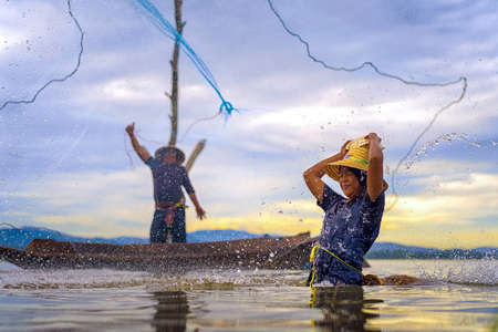 Children Fisherman Girl with catching fish splash water and fisherman throwing nets on boat on lake river thailand Stock Photo