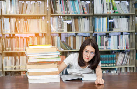 Young Girl Student with Glasses Reading book Overlap Serious, Hard Exam, Quiz, Test Sleeping headache worry in Classroom Education Library University Knowledge center Stock Photo