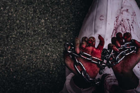 diabolic: Zombie women death  ghost standing with blood and chain, darkness background, horror halloween festival concept Stock Photo