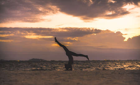 exersice: Young woman yoga exersice posting silhouette on the beach in summer