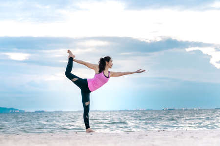 sun energy: Young asian yoga exercise with posting on the beach in summer outdoor