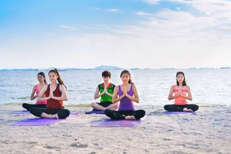 Young group yoga exercise with post on the beach in summer Banco de Imagens