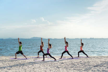 Young group yoga exercise with making warrior pose on the beach in summer
