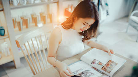 Asian young girl reading book magazine fashion smile in cafe shop with coffee brake on vacation holiday rest and relax Stock Photo