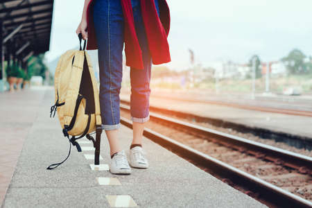 A Walking young girl tourist on side railway holding smartphone with backpack going to travel scenery town tour around at train station platform for take the rest, happy and life experience having fun
