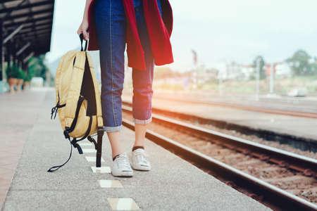 Een lopende jonge meid toerist aan de kant van de spoorweg bedrijf smartphone met rugzak gaat reis landschap stad tour rond op station station platform voor de rest, gelukkig en het leven ervaring plezier hebben Stockfoto
