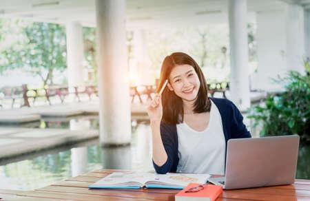 Jong meisje student glimlachend schrijven met school mappen Boek en laptop in onderwijs campus universiteit buiten Stockfoto