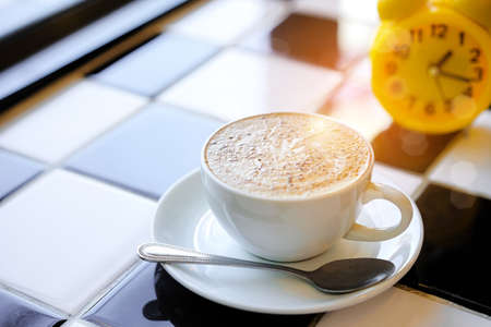 evening newspaper: Capuccino coffee and Yellow clock on White and Black Table in Cafe