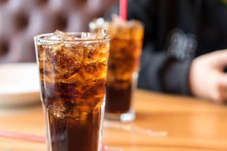 Double boisson gazeuse soda frais gazéifié, plat blanc sur la table en bois avec bel homme assis canapé brun dans une pizzeria Banque d'images