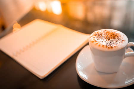 evening newspaper: Cappuccino coffee and notebook on table in the morning