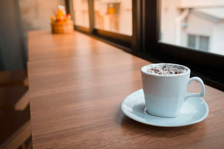 evening newspaper: Cappuccino coffe on wood table in the morning Stock Photo