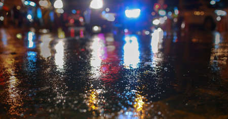 when: Water on street and color lighting, traffic night illuminated reflection liquid, using the car on the road when it weather rainy season accident brake at modern city. Stock Photo
