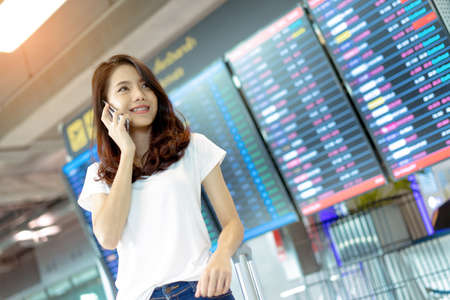Young girl asian traveler using mobile smartphone with carrying hold suitcase luggage and passenger for tour travel booking ticket flight in airport international vacation time in holiday relaxation. Stock Photo