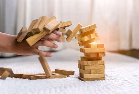 Young man pulling out wood block fail on building tower at home and drape change, choice business risking dangerous project plan failure construction  Stock Photo