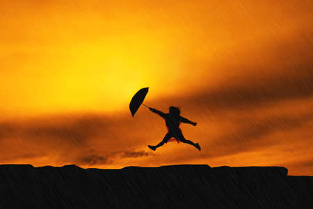 Young girl asian jumping with raincoat and umbrella on mountain in the rainy season silhouette Stock Photo