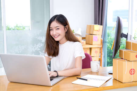 Young asian girl freelancer business private working at home office with laptop, note, coffee, packaging delivery online market on purchase orders to customer. Banco de Imagens