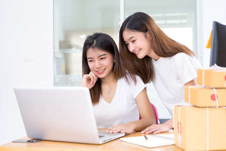 Young asian girl together freelancer business private working at home office with laptop, note, mobile, packaging delivery online market on purchase checking orders to customer. Reklamní fotografie
