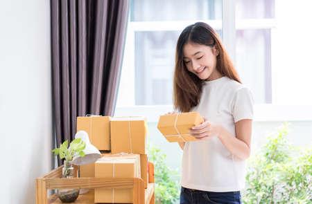 Jonge Aziatische meisje freelancer zakelijke particuliere werken thuis kantoor met opmerking, post-it, verpakking sorteren box levering online markt op bestellingen tot klant. Stockfoto