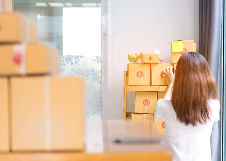 Young asian girl freelancer business private working at home office holding packaging sort box delivery online market on purchase orders to customer.