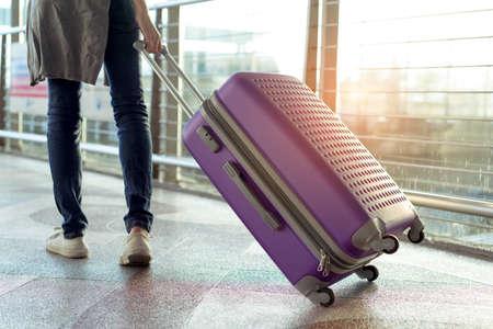 Jonge meisjesreiziger die met de dragende bagage en de passagier van de greepkoffer voor reisreis het boeken kaartje vlucht in tijd van de luchthaven de internationale vakantie in vakantierust en ontspanning lopen.