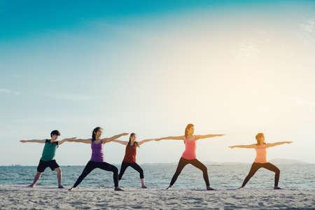Jonge groepsman en vrouwenyoga de praktijk op matontspanning in klassenoefening met stelt fitness sport voor gezond op het strand en de kust moderne stad bij zonsopgang ontspant