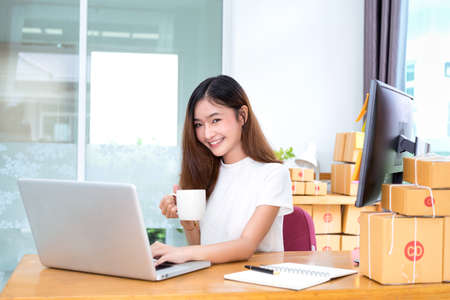 Young asian girl freelancer small business private working at home office with laptop, note, coffee, packaging delivery online market on purchase orders to customer.